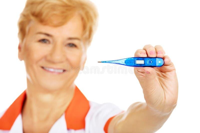 Doutor ou enfermeira fêmea idosa do sorriso que guardam o termômetro fotos de stock