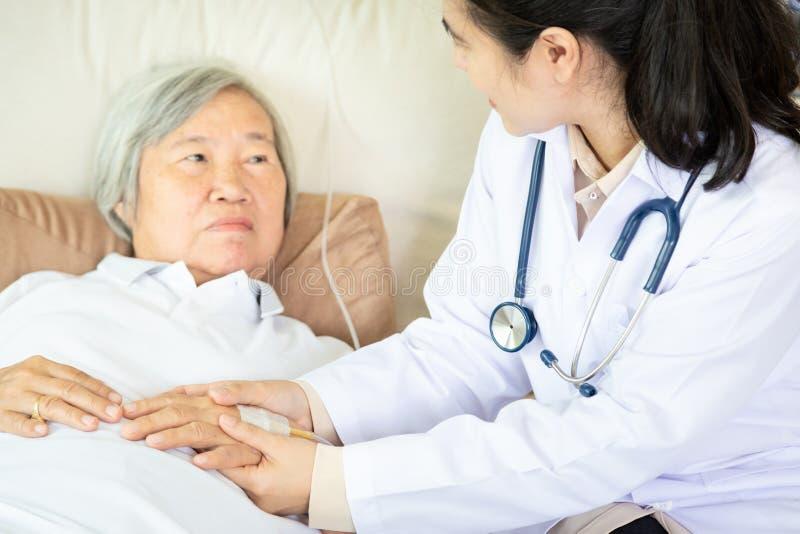 Doutor ou enfermeira fêmea médica que guardam as mãos pacientes superiores e que consolam a na cama de hospital ou na casa, mão d imagens de stock royalty free