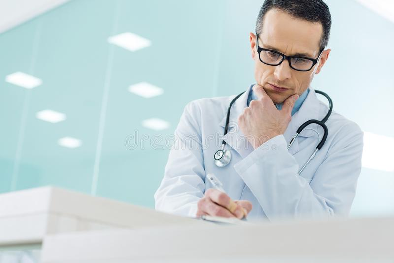 doutor pensativo no revestimento branco com diagnóstico da escrita do estetoscópio imagem de stock