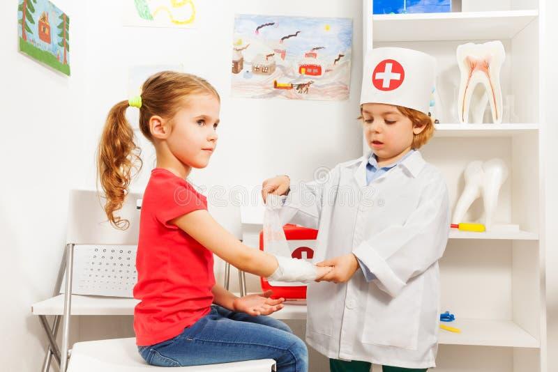 Doutor pequeno do pediatra que enfaixa o braço da menina foto de stock