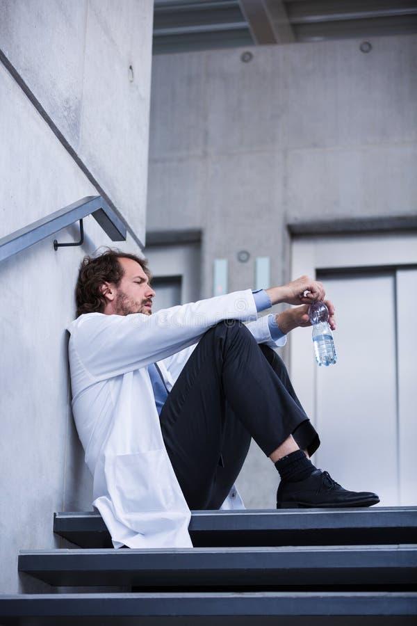 Doutor preocupado que senta-se em escadas fotografia de stock royalty free