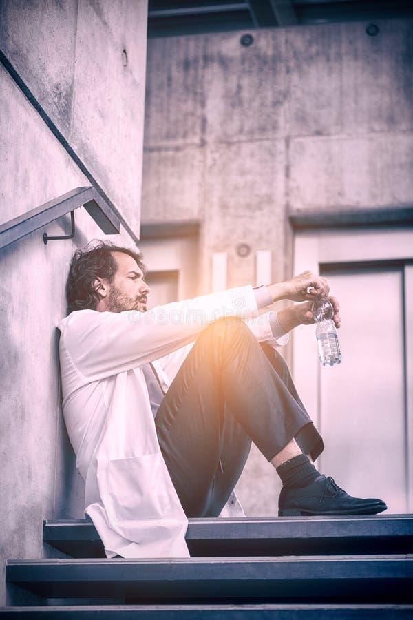 Doutor preocupado que senta-se em escadas fotografia de stock