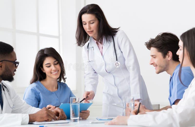 Doutor principal que discute o diagnóstico com os internos e os médicos imagem de stock