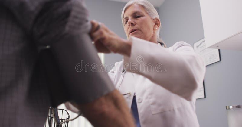 Doutor profissional que mede a pressão sanguínea de homem superior imagem de stock royalty free
