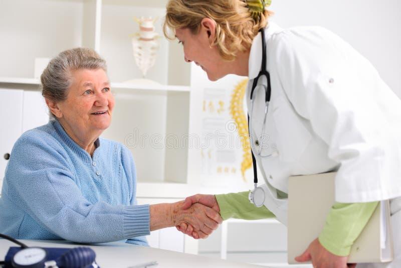 Doutor que agita as mãos ao paciente fotografia de stock