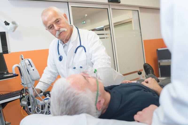 Doutor que ajuda ao paciente na máscara de respiração fotografia de stock