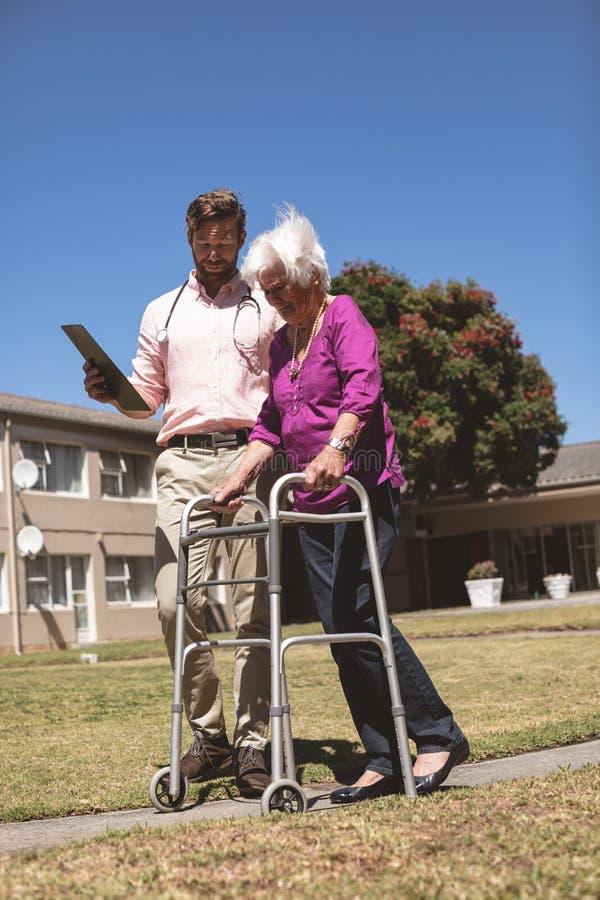 Doutor que ajuda a mulher superior com seu caminhante no lar de idosos do quintal imagem de stock