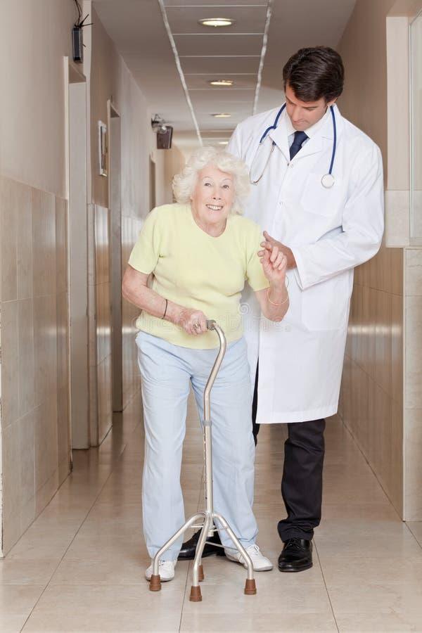 Doutor que ajuda a vara de passeio paciente do uso imagem de stock