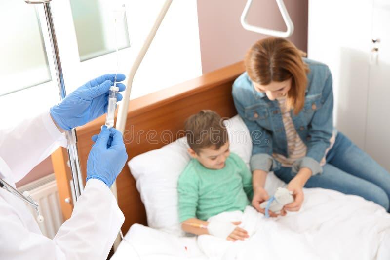 Doutor que ajusta o gotejamento intravenoso para pouca crian?a no hospital durante o pai imagens de stock