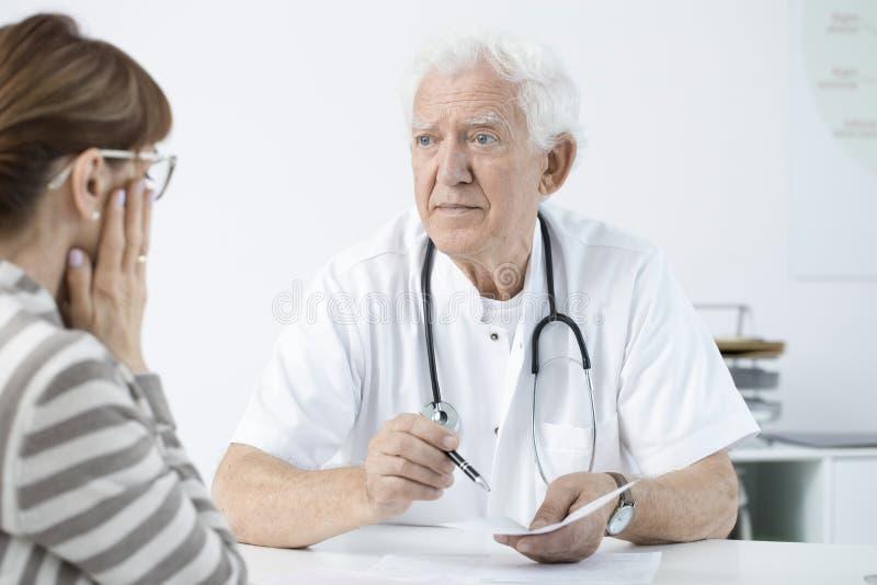 Doutor que anuncia más notícias imagens de stock royalty free