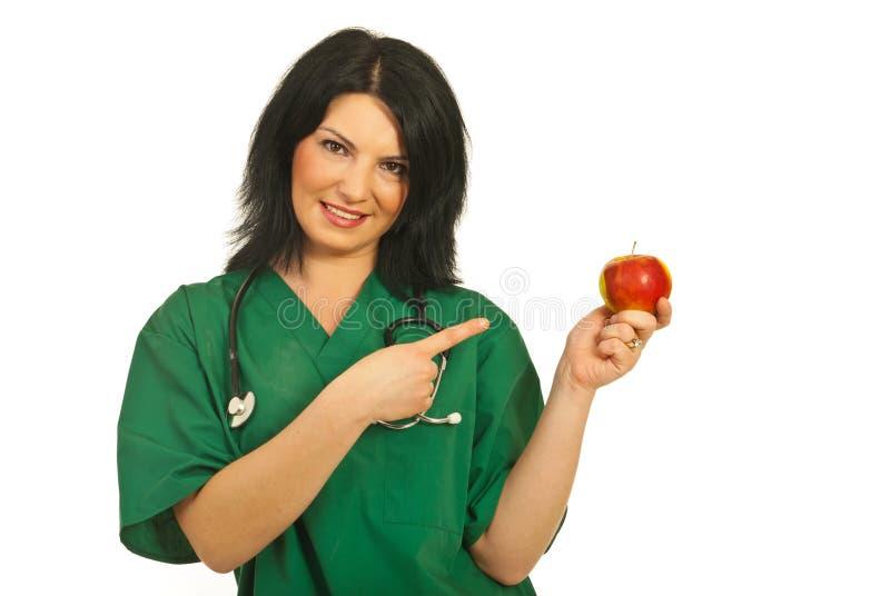 Doutor que aponta à maçã imagem de stock