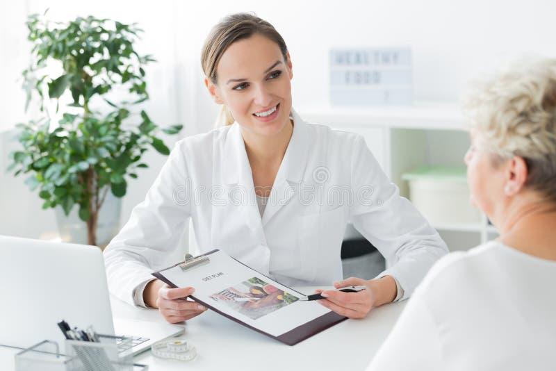 Doutor que apresenta o plano personalizado da dieta foto de stock