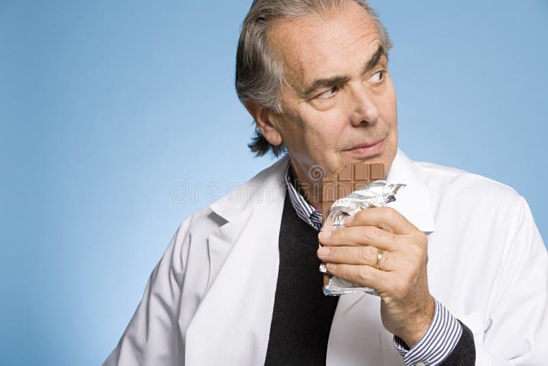 Doutor que come o chocolate fotos de stock royalty free
