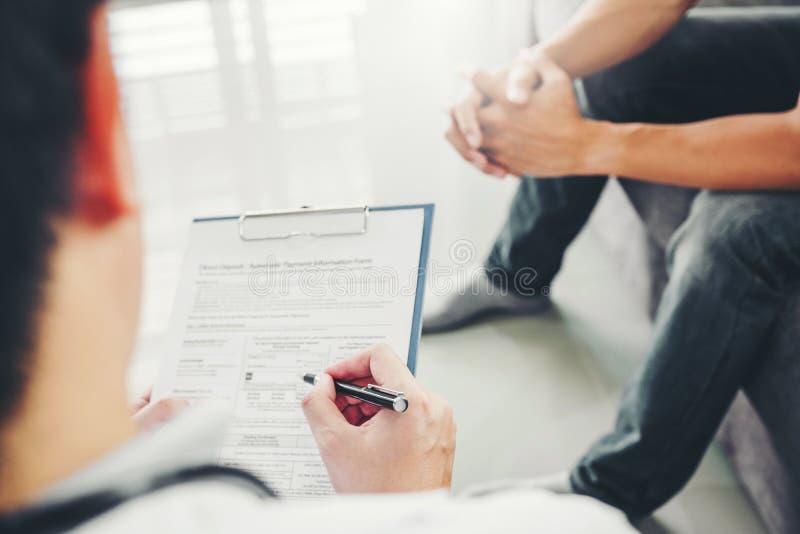 Doutor que consulta e que examina diagnóstico com doença paciente da saúde dos homens e escrita na informação de registro da pres foto de stock