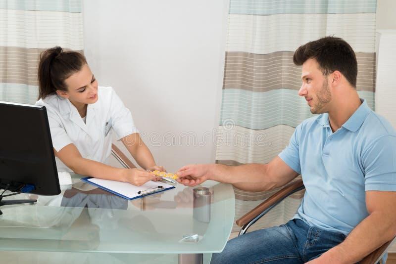 Doutor que dá comprimidos ao paciente masculino foto de stock