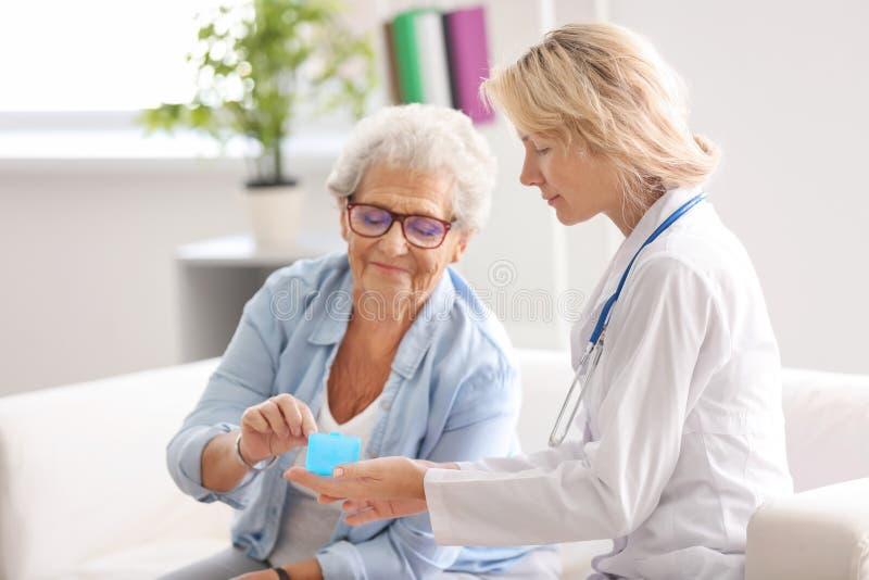 Doutor que dá a medicina à mulher superior em casa imagens de stock
