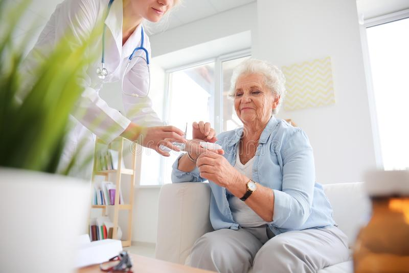Doutor que dá a medicina à mulher superior em casa fotografia de stock