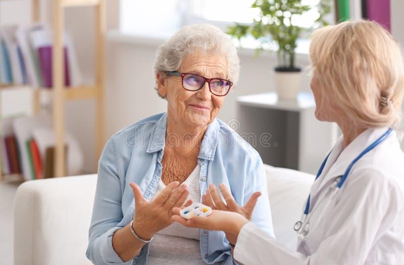 Doutor que dá a medicina à mulher superior em casa foto de stock
