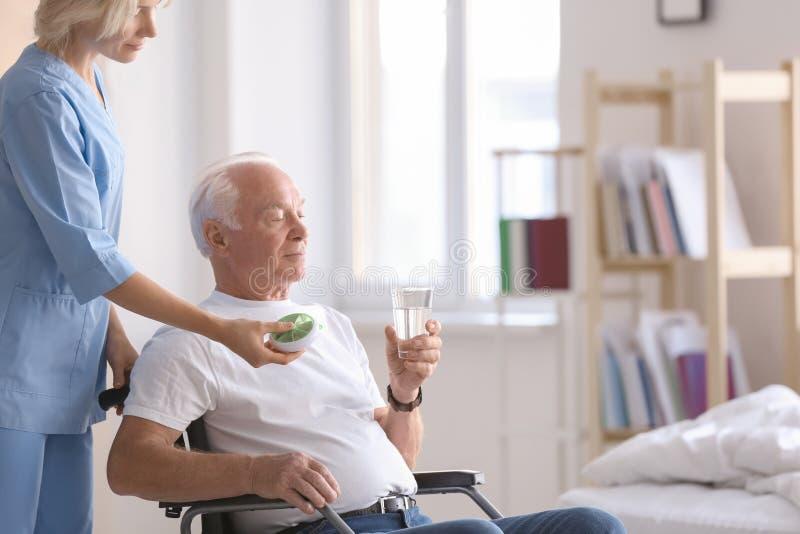 Doutor que dá a medicina ao homem superior em casa foto de stock royalty free