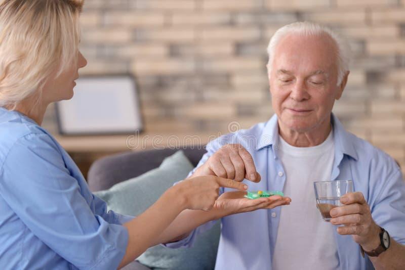 Doutor que dá a medicina ao homem superior em casa fotos de stock royalty free
