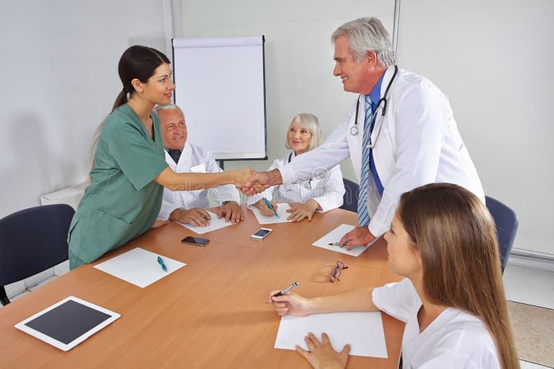 Doutor que dá o aperto de mão ao membro da equipa novo imagens de stock royalty free