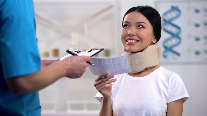 Doutor que dá a prescrição à mulher feliz na medicina barata do colar cervical da espuma fotos de stock