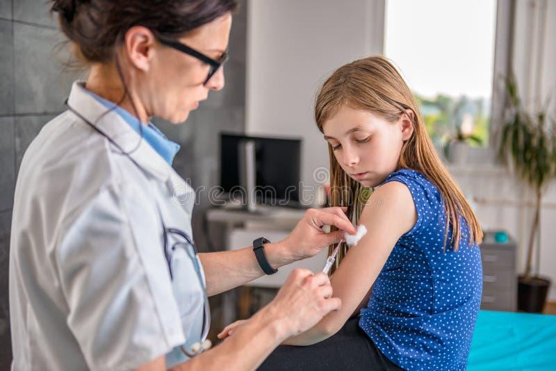 Doutor que dá a uma moça um tiro vacinal fotografia de stock royalty free