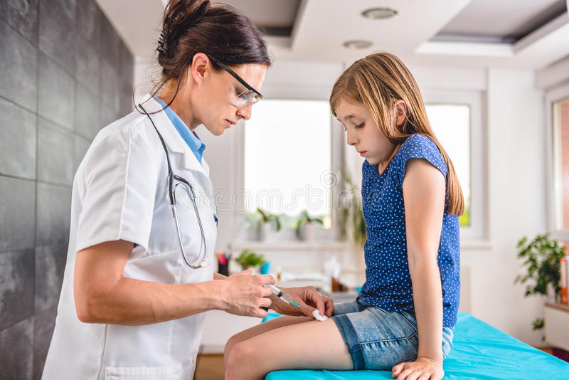 Doutor que dá a uma moça um tiro vacinal imagens de stock
