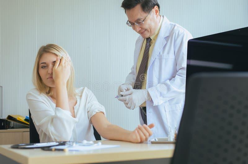Doutor que dá a vacina à mulher paciente amedrontada com injeção ou à seringa no hospital imagens de stock