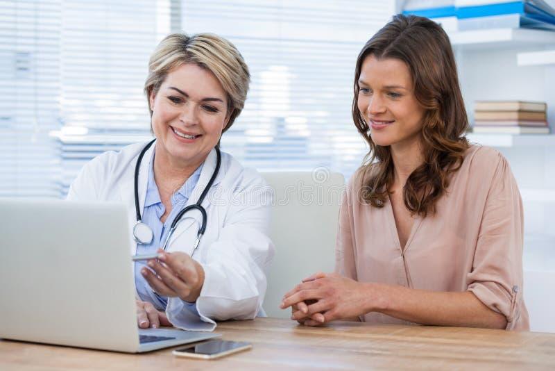 Doutor que discute com o paciente sobre o portátil imagens de stock