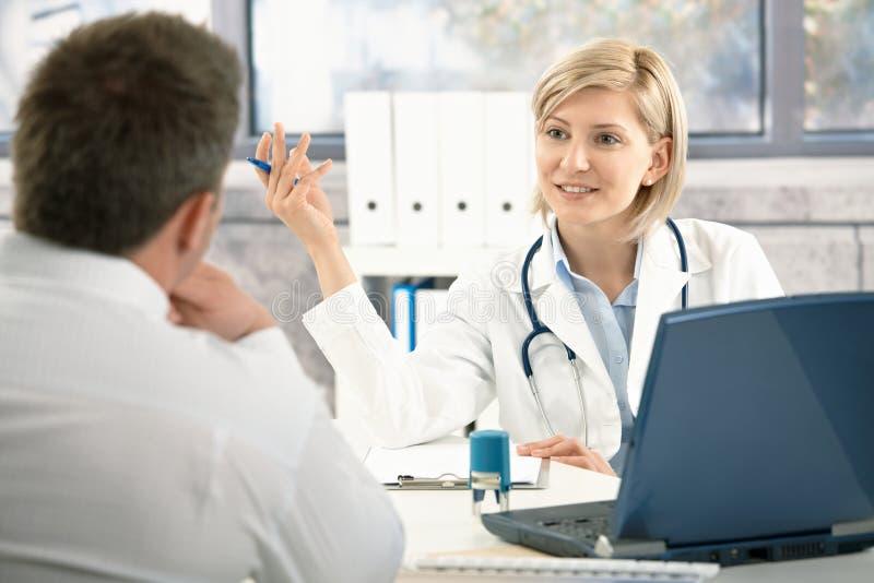 Doutor que discute o diagnóstico com o paciente fotografia de stock