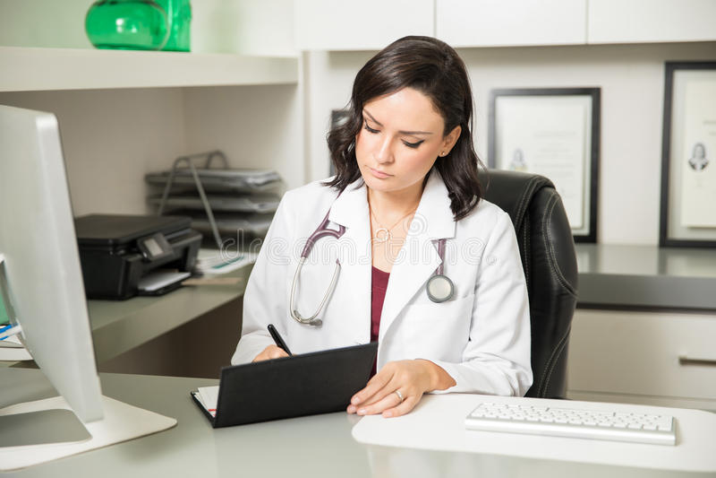 Doutor que escreve uma prescrição médica imagem de stock