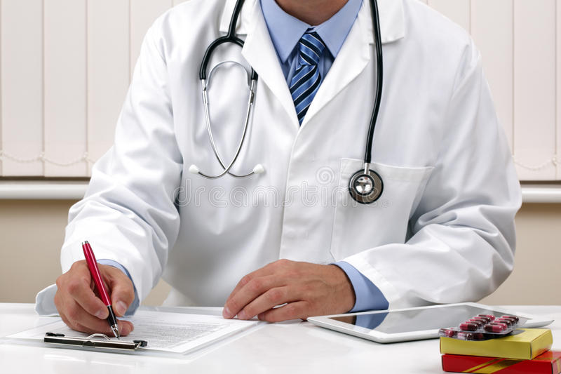 Doutor que escreve uma prescrição ou umas notas médicas foto de stock