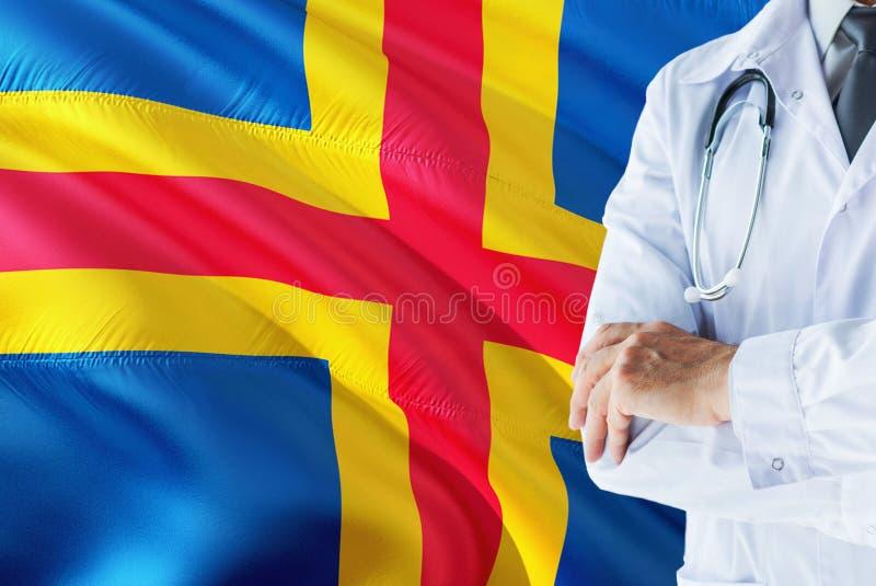 Doutor que est? com o estetosc?pio no fundo da bandeira das ilhas de Aland Conceito de sistema de sa?de nacional, tema m?dico imagem de stock royalty free