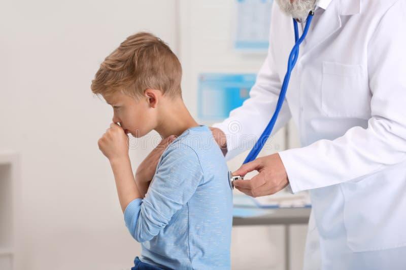 Doutor que examina tossindo o rapaz pequeno foto de stock