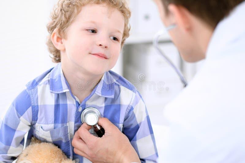 Doutor que examina um paciente da criança pelo estetoscópio fotos de stock