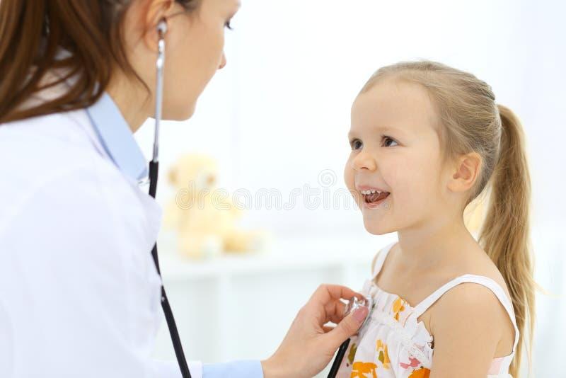 Doutor que examina uma menina pelo estetosc?pio Paciente de sorriso feliz da crian?a na inspe??o m?dica usual Medicina e fotografia de stock royalty free