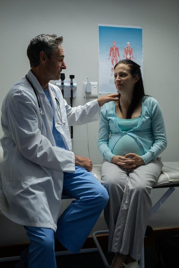 Doutor que examina uma mulher gravida no hospital imagem de stock