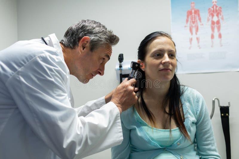 Doutor que examina uma mulher gravida no hospital imagens de stock