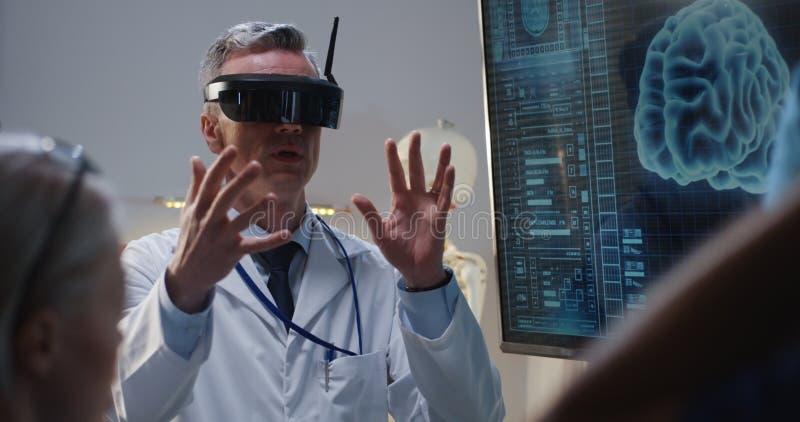 Doutor que explica com auriculares de VR fotos de stock