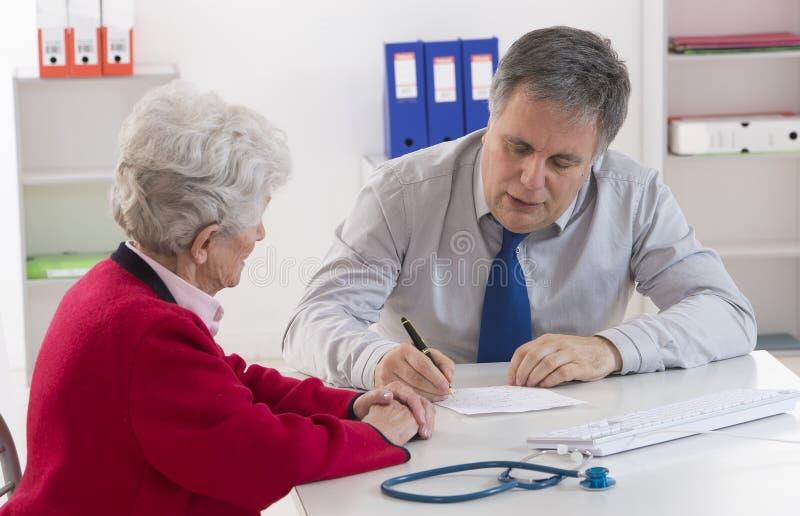 Doutor que explica o diagnóstico a seu sênior foto de stock royalty free