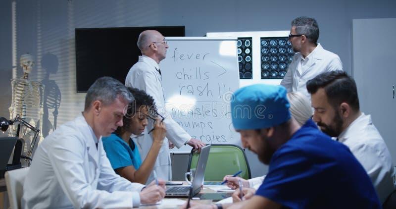 Doutor que explica o diagn?stico a seus colegas fotos de stock