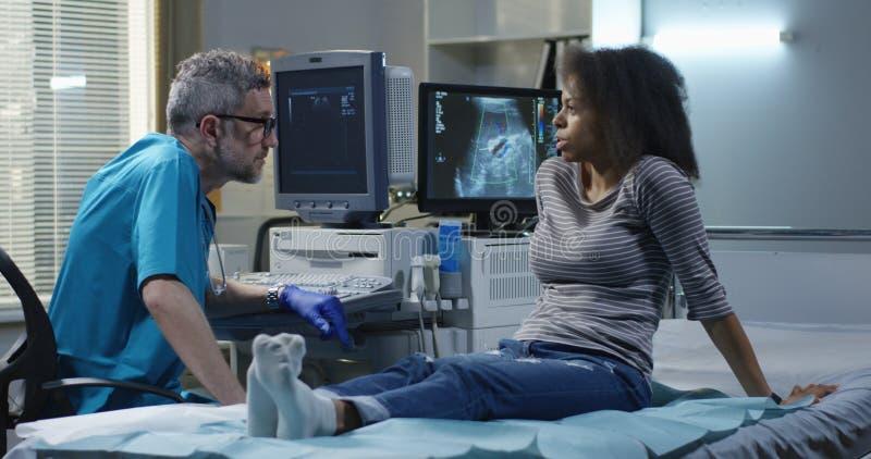Doutor que explica o diagn?stico a uma mulher fotos de stock