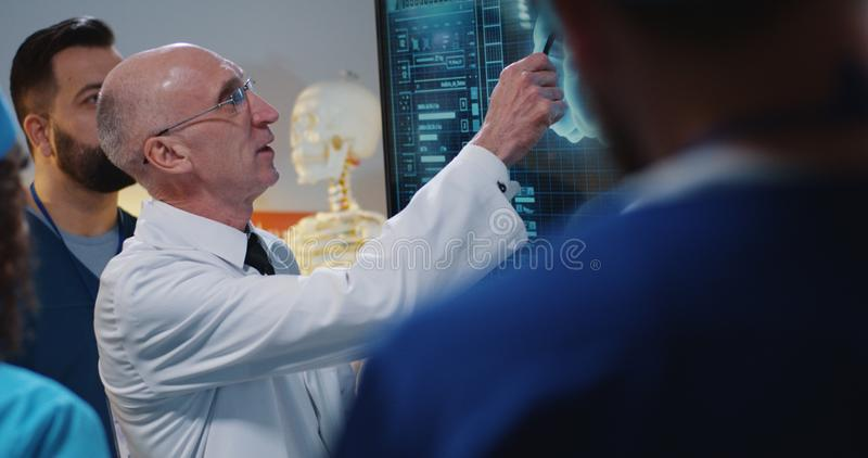 Doutor que explica a seus colegas imagens de stock