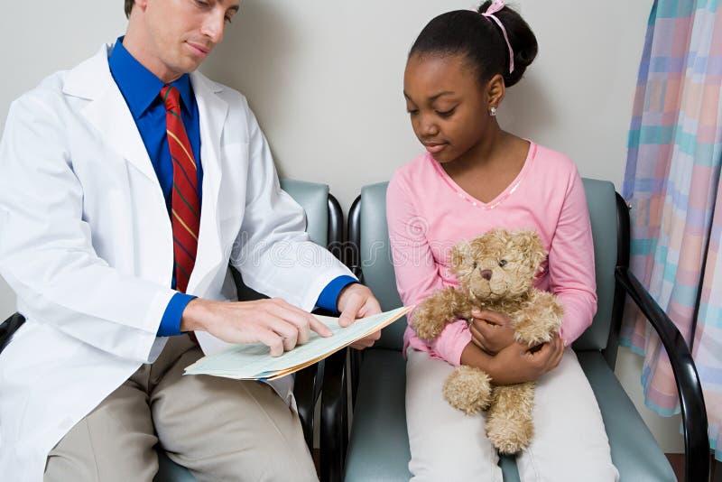 Doutor que fala à menina imagens de stock royalty free