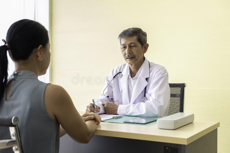 Doutor que fala ao paciente da mulher, recomenda que pacientes fotografia de stock