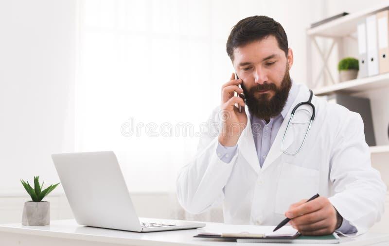 Doutor que fala com seu paciente e que escreve para baixo o diagnóstico fotografia de stock