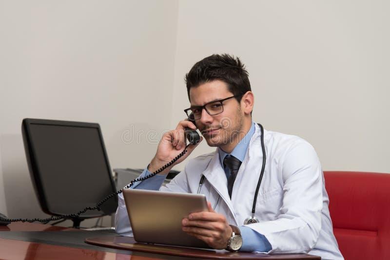Doutor que fala no telefone e que usa o computador fotos de stock