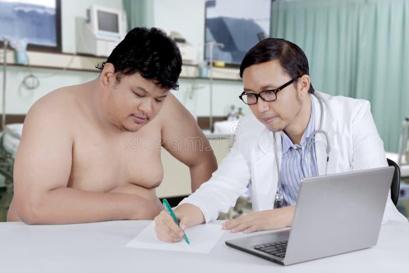 Doutor que fala a um paciente excesso de peso foto de stock