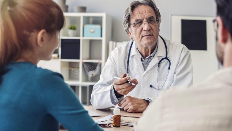 Doutor que fala um par novo de pacientes fotografia de stock royalty free